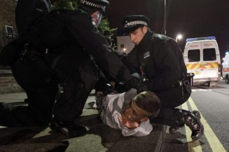 Police officers detain a man in Eltham, south London